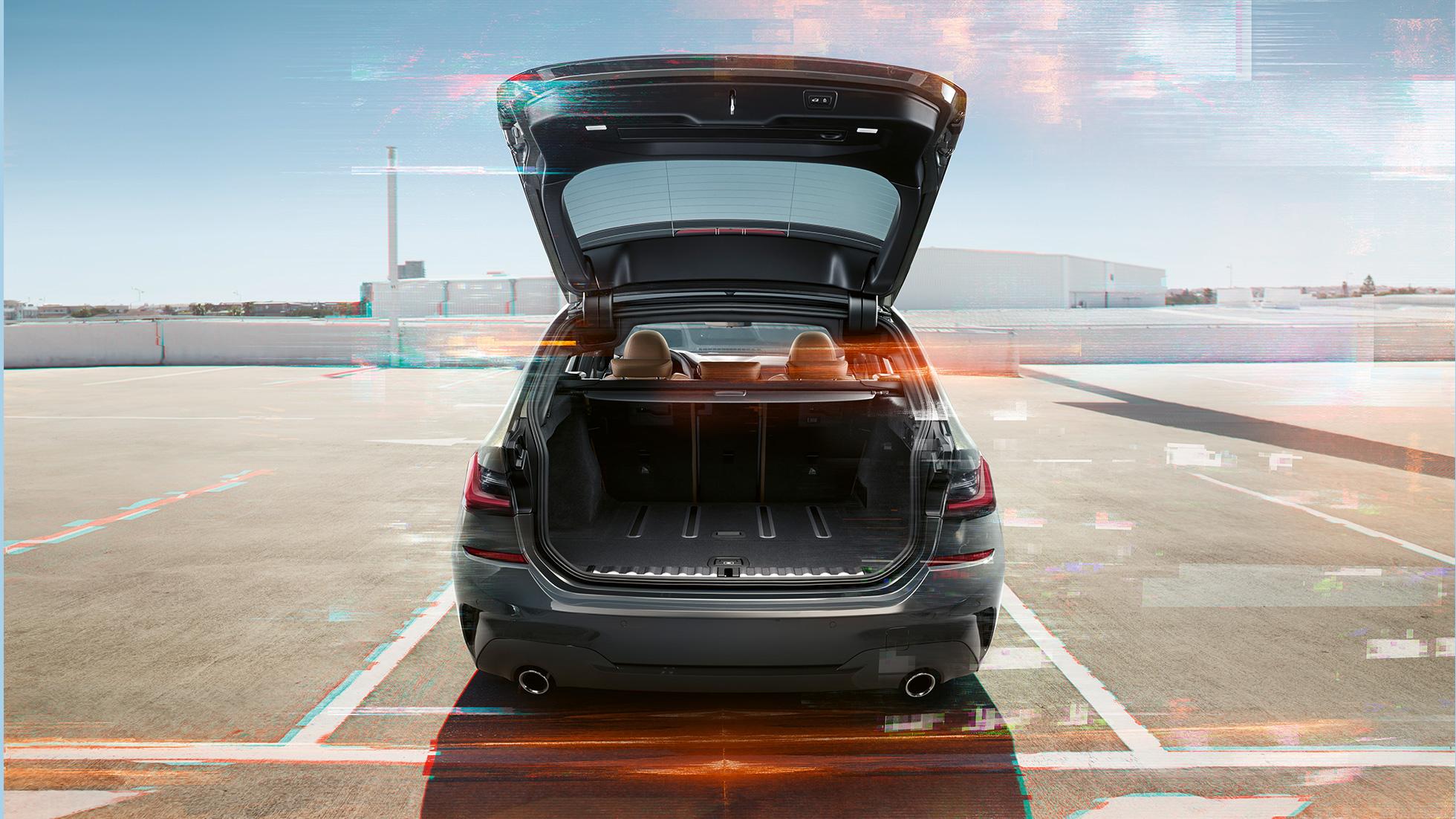 BMW Série 3 Touring, prise de vue de la poupe avec hayon ouvert sur une place de stationnement dans un environnement urbain
