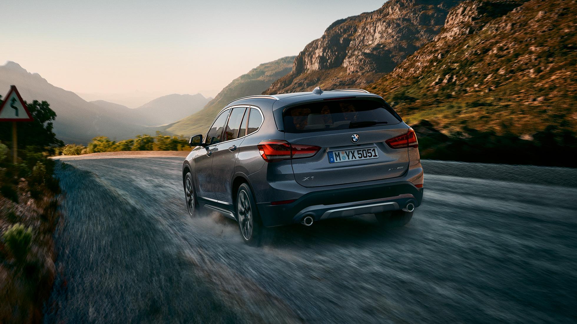 BMW X1, vue de trois quarts arrière devant le paysage montagneux.