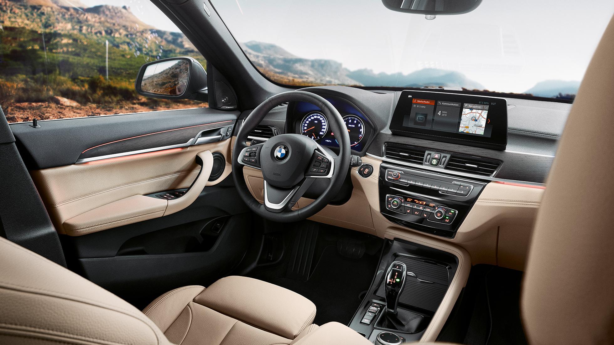 """Intérieur de la BMW X1, vue sur le Control Display de 10,25"""" dans le poste de conduite."""